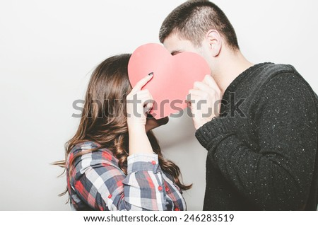 Happy couple kissing behind a red heart - stock photo
