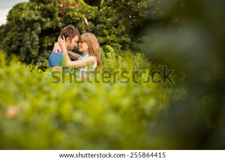 happy couple kissing in the park - stock photo