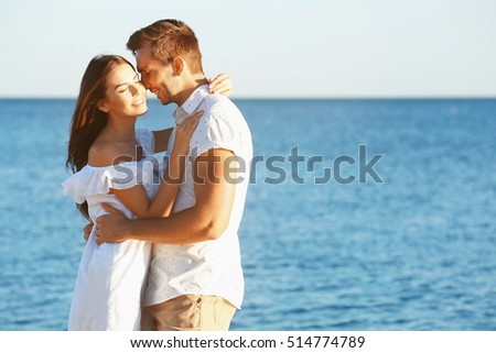 Happy couple kissing on sea background