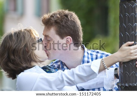 Happy couple kissing outside on a sunny summer morning