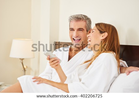 Happy couple laughing during holiday stay in hotel room - stock photo