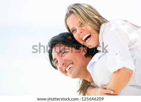 Happy couple laughing outdoors enjoying their time together - stock photo