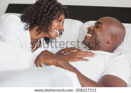 Happy couple laughing together in bed at home in the bedroom