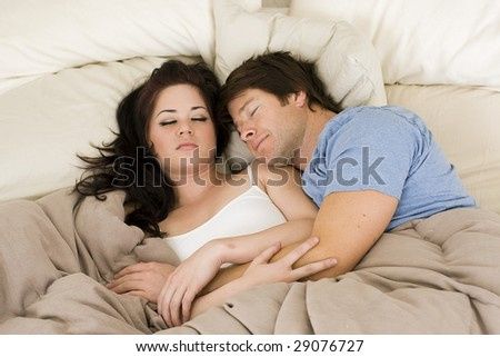 Happy couple laying in bed - stock photo