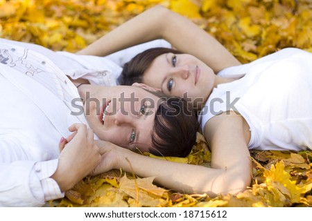 happy couple laying on yellow leaves - stock photo