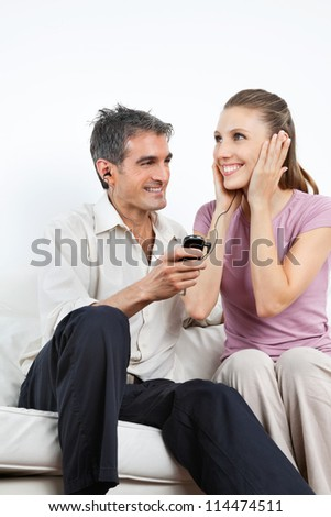 Happy couple listening music together on cell phone while sitting on sofa
