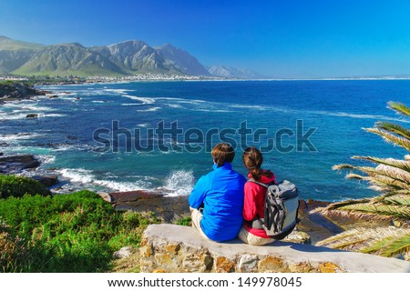 Happy couple looking at beautiful ocean view in Hermanus, romantic vacation in South Africa  - stock photo