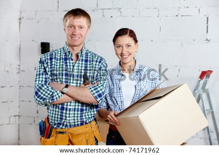 Happy couple looking at camera in new house - stock photo