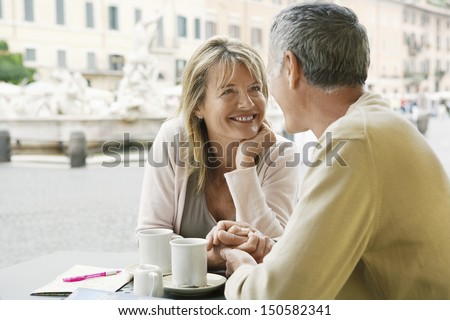 Happy couple looking at each other at outdoor cafe in Rome - stock photo