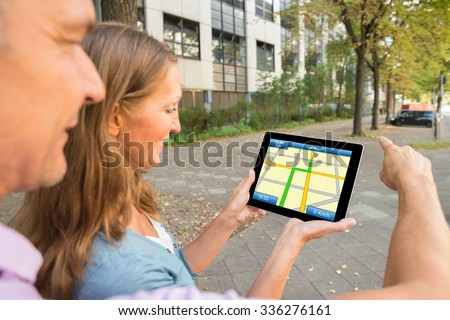 Happy Couple Looking At Gps Map On Digital Tablet - stock photo