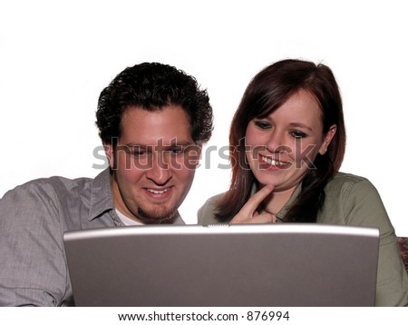 Happy couple looking at laptop computer isolated on white - stock photo