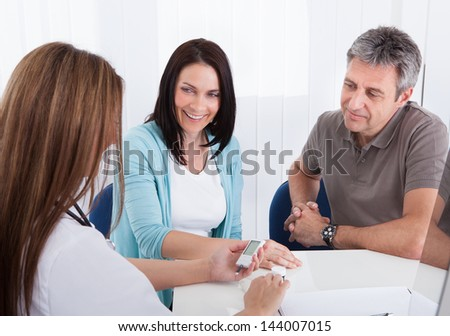 Happy Couple Looking At Results Held By Doctor