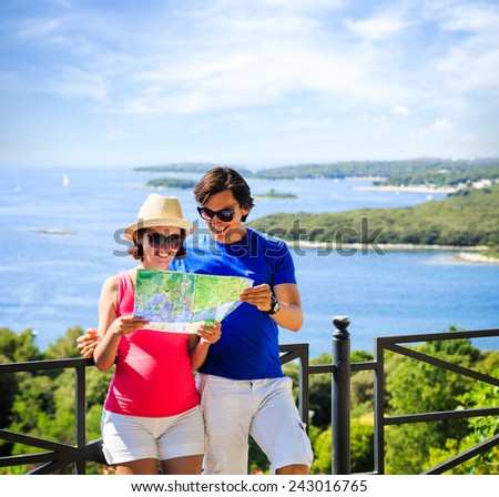 Happy Couple Looking at the Map. Summer Sea Background with Islands. Copy Space. Travel and Vacation Concept. - stock photo