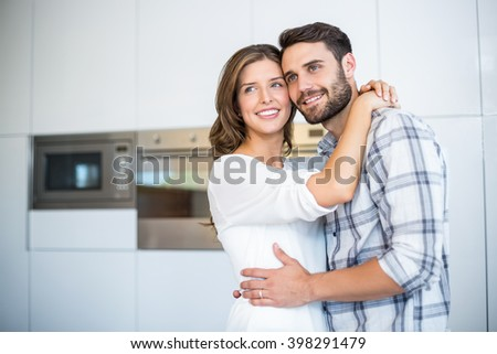 Happy couple looking away while embracing in kitchen at home - stock photo