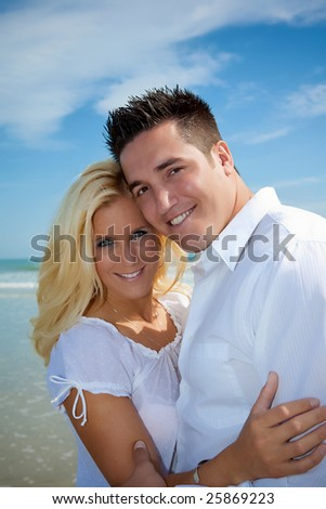 Happy couple looking into camera, standing on a beach. - stock photo