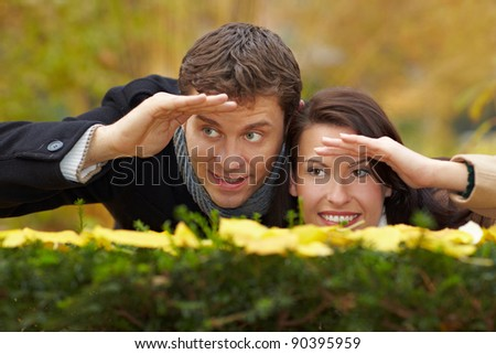 Happy couple looking over a hedge in autumn - stock photo