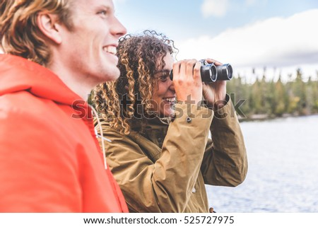 Happy couple looking through a binoculars. The woman is holding the binoculars, the man is standing next to her and looking away. Exploration and nature concepts