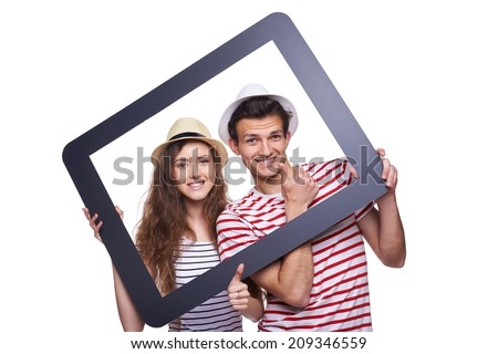 Happy couple looking through tablet frame and giving thumb up - stock photo