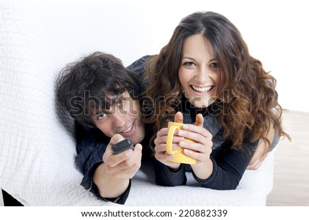 Happy couple lying down in bedroom watching television together - stock photo