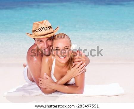 Happy couple lying down on beautiful sandy shore, having fun outdoors, spending honeymoon vacation on beach resort, love and romance concept - stock photo