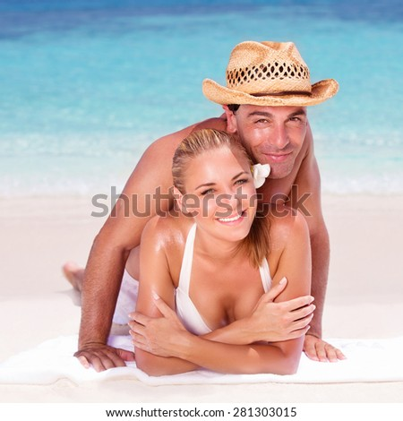 Happy couple lying down on the beautiful sandy beach, enjoying each other, spending honeymoon vacation, summer activity concept - stock photo