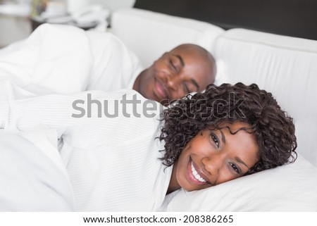 Happy couple lying in bed together at home in the bedroom - stock photo