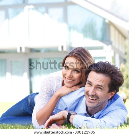 happy couple lying in front of their house - stock photo