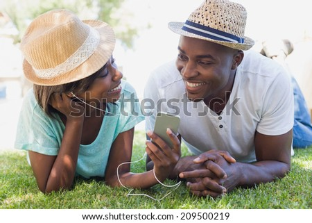 Happy couple lying in garden together listening to music on a sunny day