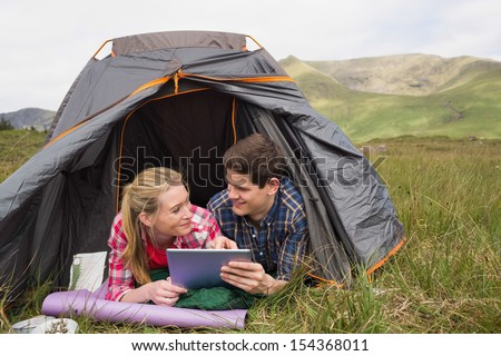 Happy couple lying in their tent and using digital tablet in the countryside - stock photo
