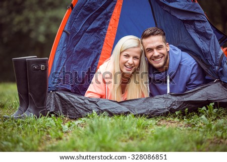 Happy couple lying in their tent in the countryside - stock photo