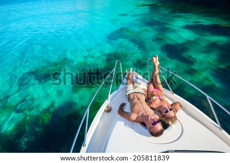 Happy couple lying on a boat at sea. Luxury vacation on a yacht in the islands. - stock photo
