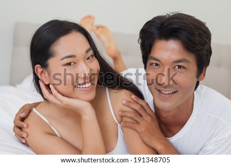 Happy couple lying on bed embracing at home in bedroom