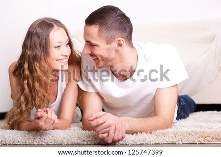 happy couple lying on carpet at home interior, looking each other