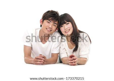 Happy couple lying on floor and smiling at camera - stock photo