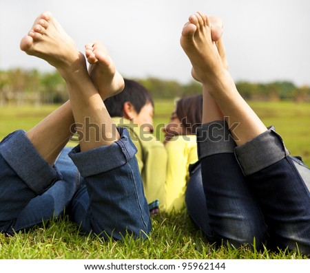 happy couple lying on the grass - stock photo