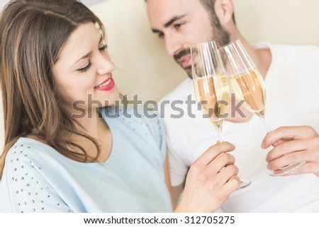 Happy couple making a toast on the bed. It could be on Valentine's day or for birthday, they're looking each other and smiling. Setting could be luxury home or hotel bedroom.