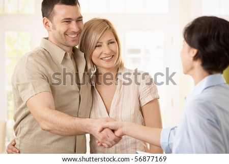 Happy couple making deal with agent, smiling man shaking hands with agent.?