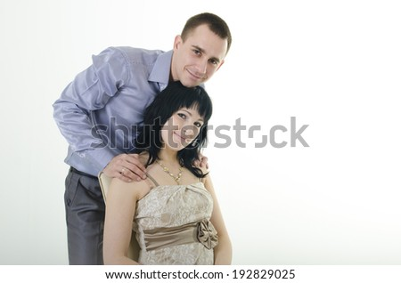 happy couple. man and woman in the studio. woman sitting on a chair, the man hugging the back - stock photo