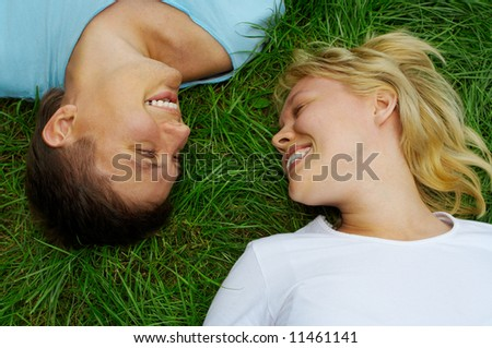 happy couple man and woman lie on green grass - stock photo