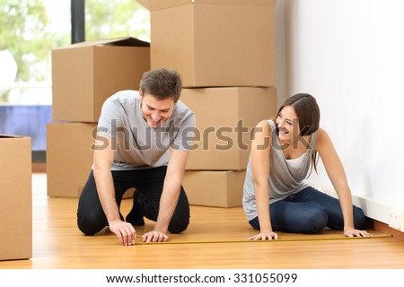 Happy couple moving house and taking measure together for the furniture - stock photo