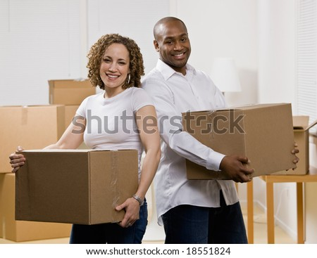 Happy couple moving into new home carrying cardboard boxes - stock photo