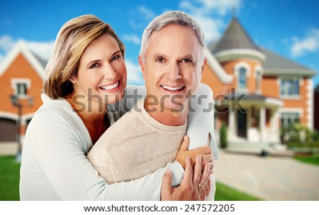 Happy couple near new home. Residential construction background. - stock photo