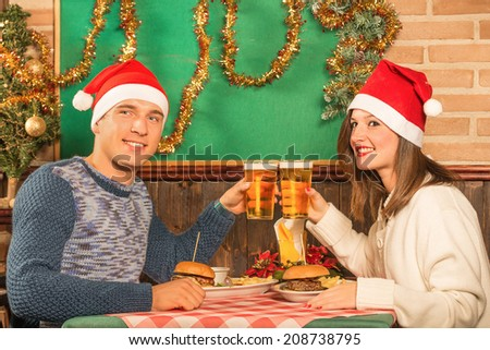 Happy couple of best friends at american restaurant with santa hats - Food and fun during Christmas holidays - Enjoying beer and hamburgers during a winter dinner - stock photo