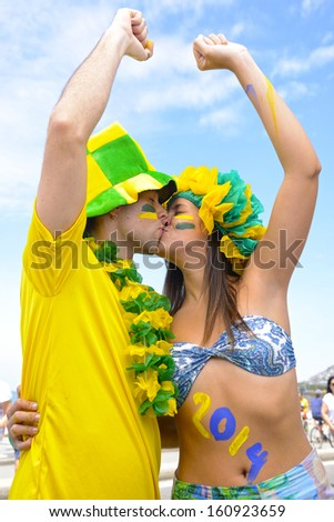 Happy couple of Brazilian soccer fans commemorating victory kissing each other. - stock photo