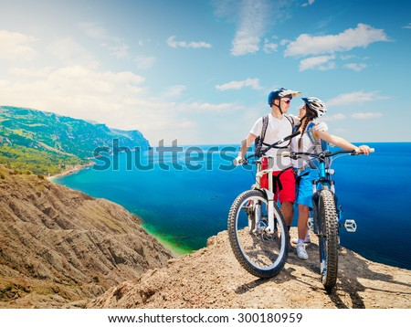 Happy couple of cyclists on mountain bikes embracing the beautiful landscape. Traveling by bicycle, man and woman. Sports lifestyle.