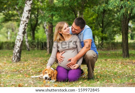 Happy couple of future parents on the walk with pet in autumn park - stock photo