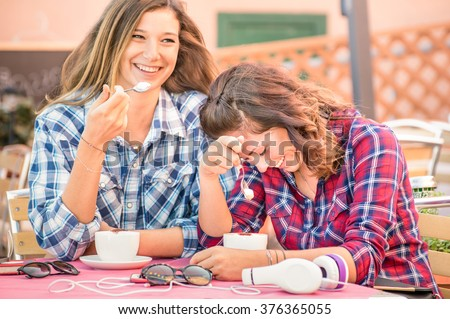 Happy couple of girlfriends drinking cappuccino and laughing together - Happiness concept with young women talking and having fun at coffee bar - Warm vintage filter with focus on girl face at right - stock photo