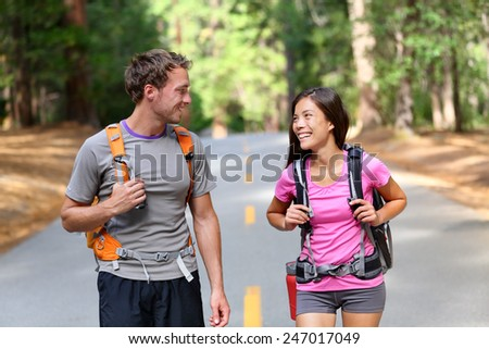 Happy couple of hikers hiking talking together, cheerful and fresh. Young active multiracial couple in outdoor activity hike in Yosemite National Park, California, USA. Asian woman, Caucasian man. - stock photo