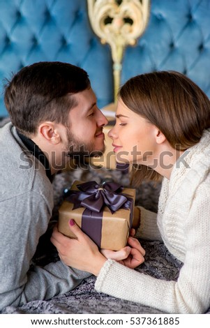 Happy couple of lovers lying on the bed. Christmas interior. Lovers together