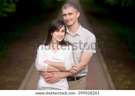 Happy couple of lovers standing in park on a date, posing, smiling in love, embracing outdoors, young man hugging his beautiful brunette girlfriend - stock photo